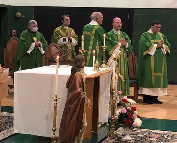 Father Thomas Alber, senior associate pastor of St. Brendan Parish in Mexico; Father Dylan Schrader, pastor; Deacon Louis Leonatti; Bishop W. Shawn McKnight; and Deacon James H. Farnell join the assembly in prayer during an Aug. 22 Mass for the 100th anniversary of St. Brendan School.