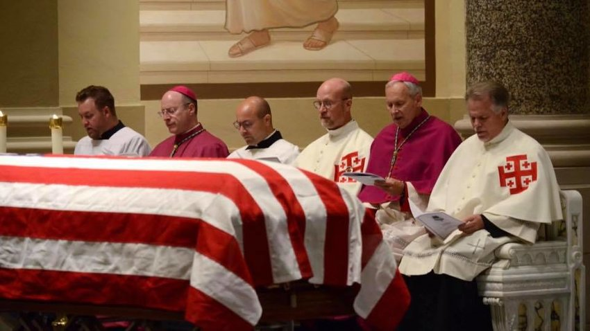 Bishop W. Shawn McKnight, second from left, prays the Office of the Dead with the priests of the Diocese of Wichita. Before them is the flag-draped coffin of Servant of God Father Emil Kapaun on Sept. 28 in the Cathedral of the Immaculate Conception.