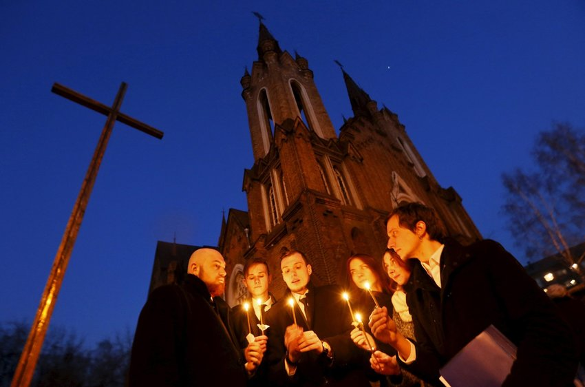 People light candles in front of a Catholic church during the Easter Vigil in the Siberian city of Krasnoyarsk, Russia, April 4, 2015.
