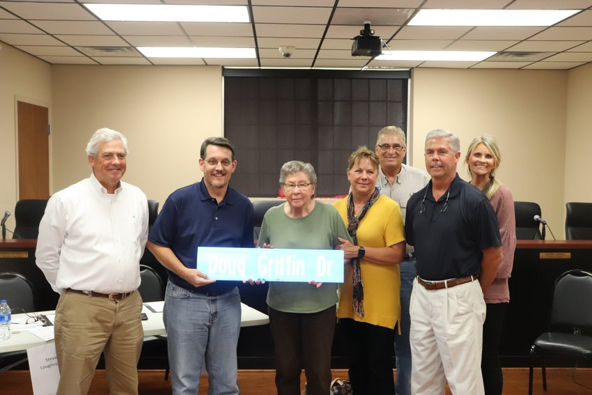Murray School Board Chairman Greg Shoemaker (second from left) presents a road sign honoring former Superintendent Doug Griffin to Griffin's widow, June, at the school board meeting on Monday. Doug Griffin, who was superintendent for 16 years, passed away in June. Pictured (from left) are current Superintendent Steve Loughridge, Shoemaker, June Griffin, Anne Griffin Childers, Billy Childers, Rhett Griffin and Sandy Griffin.