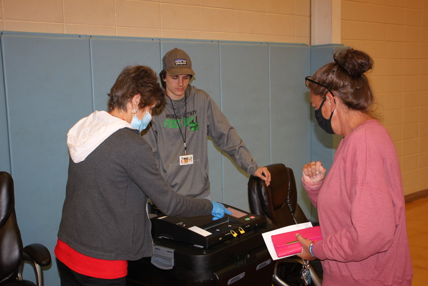 Kay Holcomb, left, and Tyson Leonard assist Carlin Johnson of Chatsworth in submitting her ballot on Tuesday.
