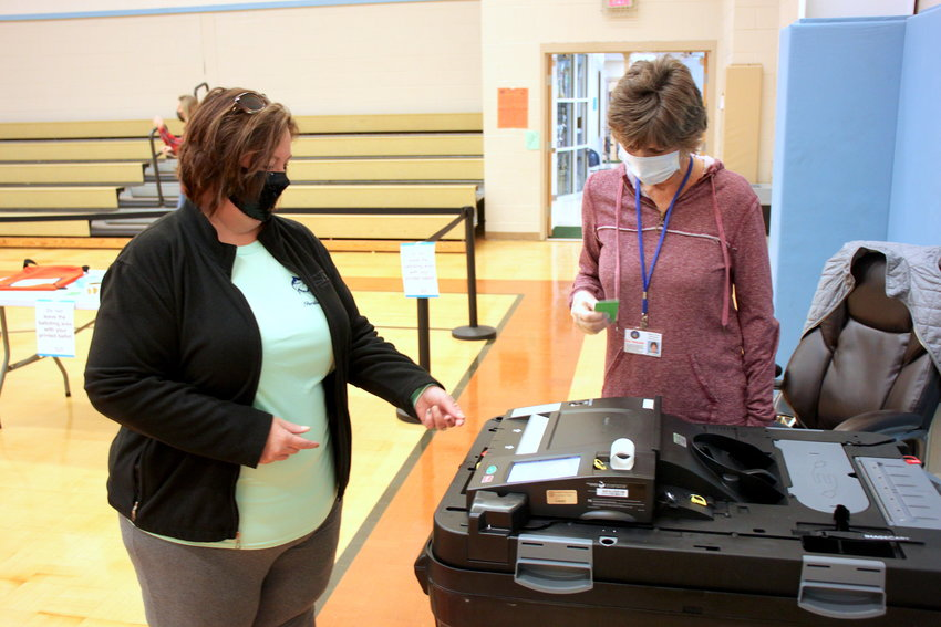 Melissa Smith, left, turns in her ballot to Kay Holcomb on Tuesday at the Eton Precinct.