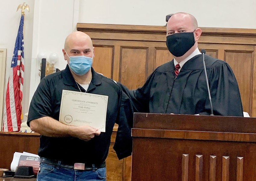 Judge Scott Minter (right) presents a diploma to Cody Ridley, the second graduate of the Conasauga Mental Health Court program.
