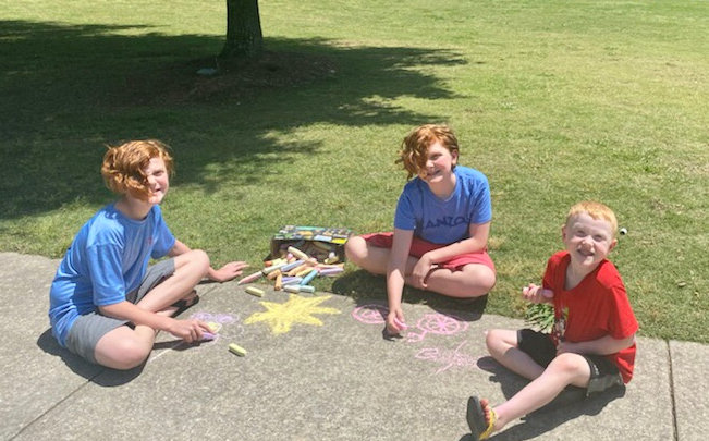 Pierce, Reagan and Ezra Bailey practice their chalk artistry in preparation for the Spring Art Walk in the Park on Saturday. The public is invited to participate in the event.