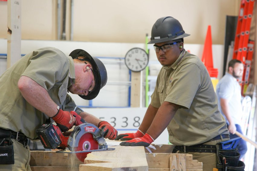 GNTC student Jonathan Pearson (left) makes cuts to a board while Brandon Najera holds the plank steady. The two students made up half of GNTC's TeamWorks team that earned a gold medal at the SkillsUSA National Leadership and Skills Conference this month.