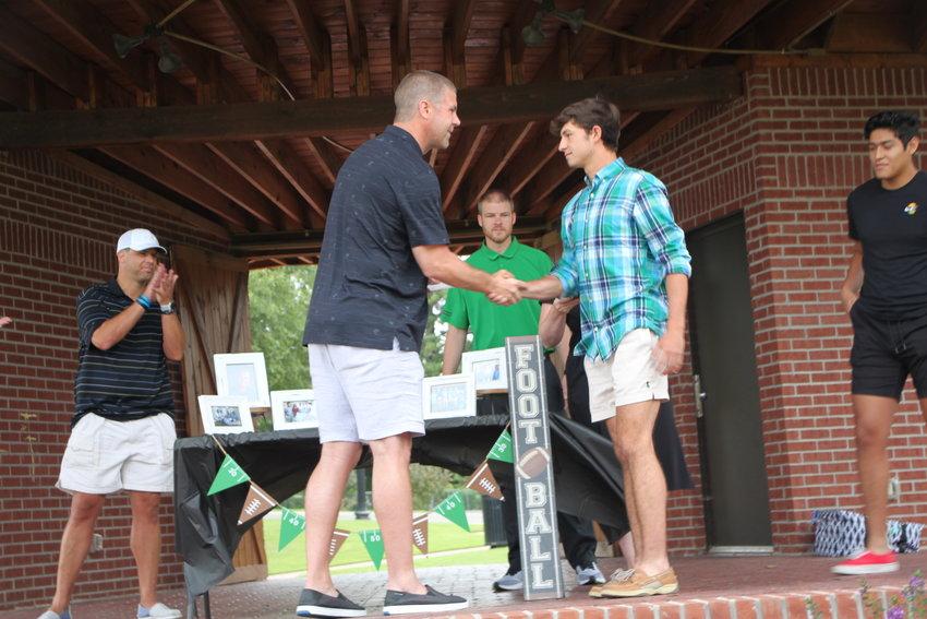 Billy Napier, left, congratulates Davis Redwine on winning a scholarship. Kurt Napier, looks on.