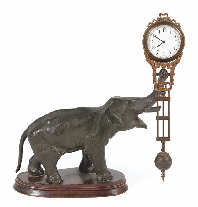 This elephant is swinging the clock, but there doesn't seem to be anything making it move. That is why it is known as a swinger or mystery clock. It is 11 inches tall.