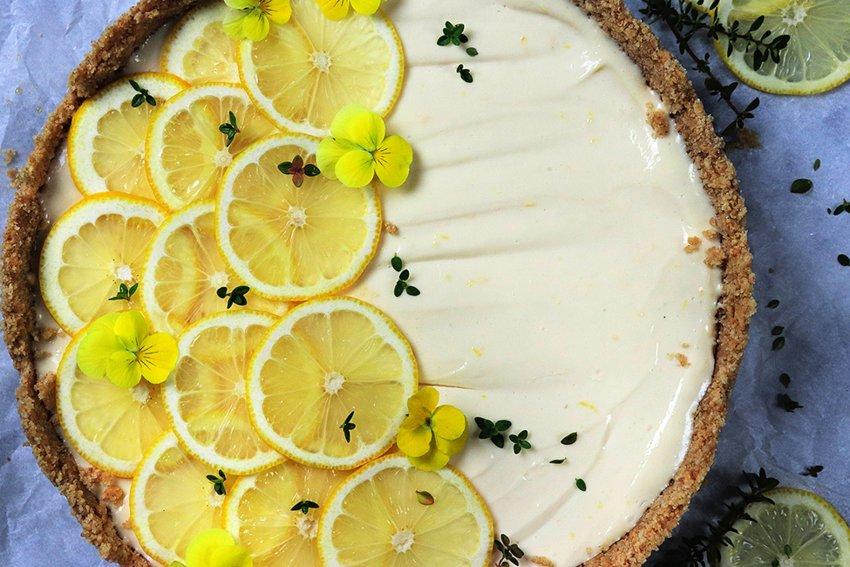 Fresh lemon cheesecake garnished with lemon slices, lemon thyme and edible flowers