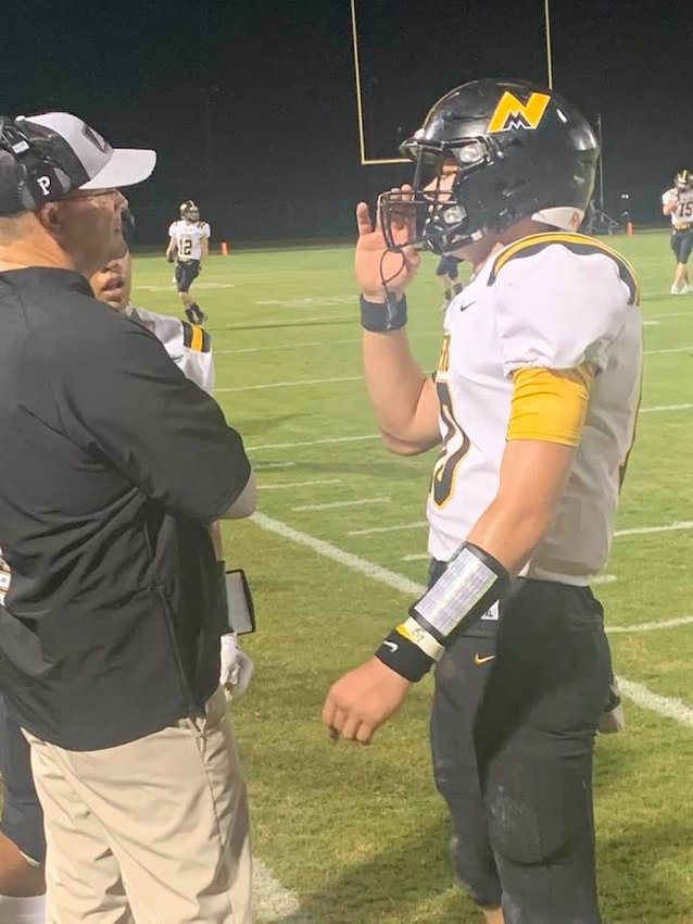 Coach Preston Poag talks with quarterback Seth Griffin.