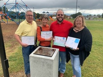 From left, Wayne McDaniel, Nancy McDaniel Shipley, Judy McDaniel Lowery and David McDaniel behind the memorial plaque at Spring Place Elementary School playground, which their parents helped build.