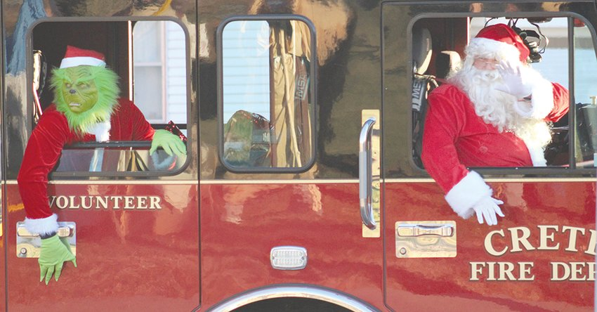 Santa Claus and the Grinch take a cruise around Crete in a fire truck. The two got the full experience with lights and sirens escorting them around town while they waved at people.