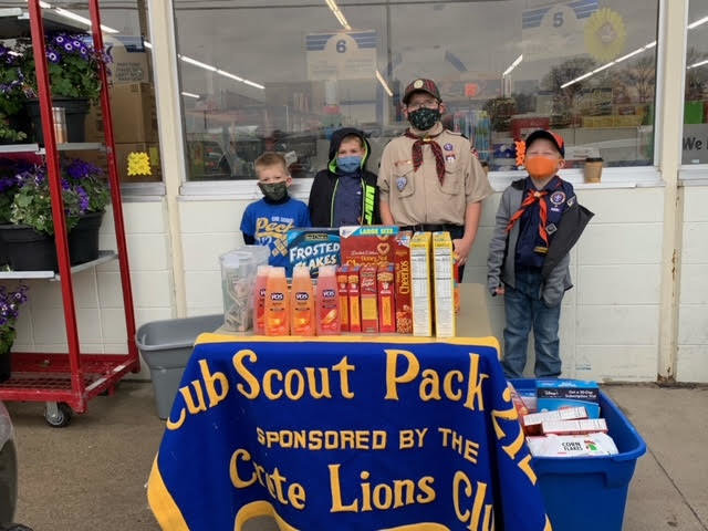 "Crete Cub Scouts, from left, Braysen Pieper, Jon Murphy, Emmett Pieper and Alex Hesser were involved in the ""Scouting for Food"" project April 17 to collect money and food for local foodbanks."