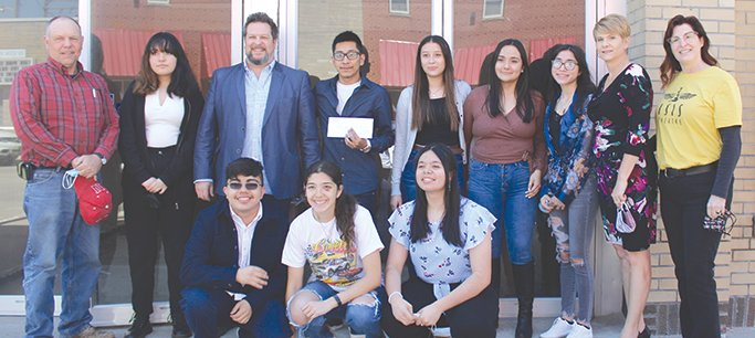 Blue River Arts Council representatives Shaylene Smith and Julie Fahrlander, far right, stand with Sen. Tom Brandt, far left, and the Foreign Film Club's sponsor and students in the club as the students present the money to be donated to BRAC for Isis Theater Renovations.