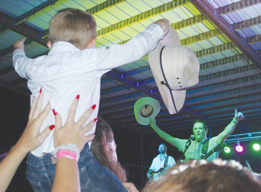 A young fan and Tracy Byrd salute each other near the conclusion of Byrd's performance July 16 at the Saline County Fair.