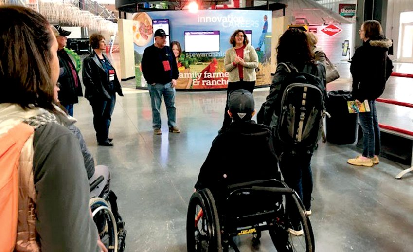 Exeter native Sarah Polak, center, leads a group through the Raising Nebraska exhibit in Grand Island. Polak serves as the experience coordinator for the center, which focuses on Nebraska agriculture.