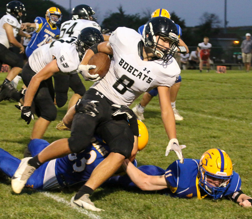 Breckan Schluter of EMF turns the corner against Tri County as defenders Cael Washburn (33) and Dusty Kapke (11) try to slow him down Sept. 17.