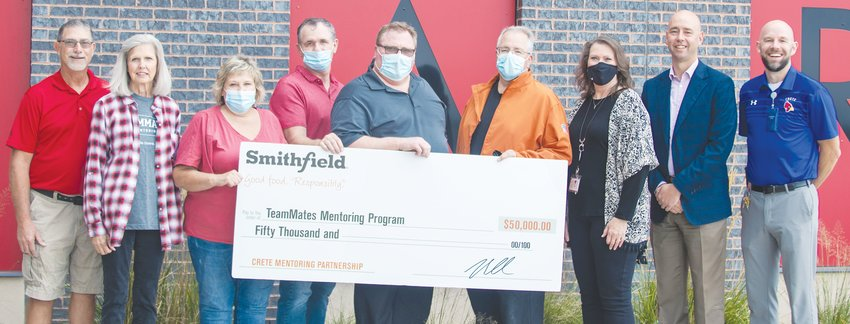 Paul Doremus, fourth from right, plant manager of Smithfield's Crete facility, presents a $50,000 donation on behalf of the company to Zoe White, third from right, program coordinator for TeamMates Mentoring Program, members of the TeamMates board and school administration in front of Crete High School.