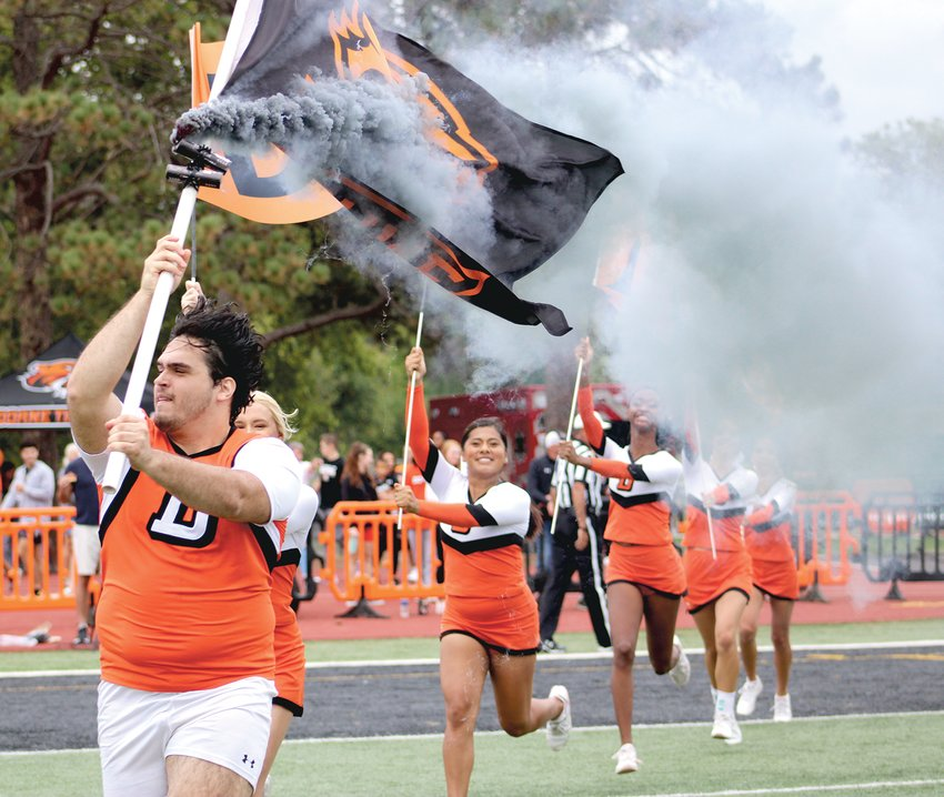 Doane cheerleader lead the football huddle onto the field with black smoke and Doane flags as the pep band played loud and proud, welcoming the football team onto the field for the Doane 2021 homecoming game.