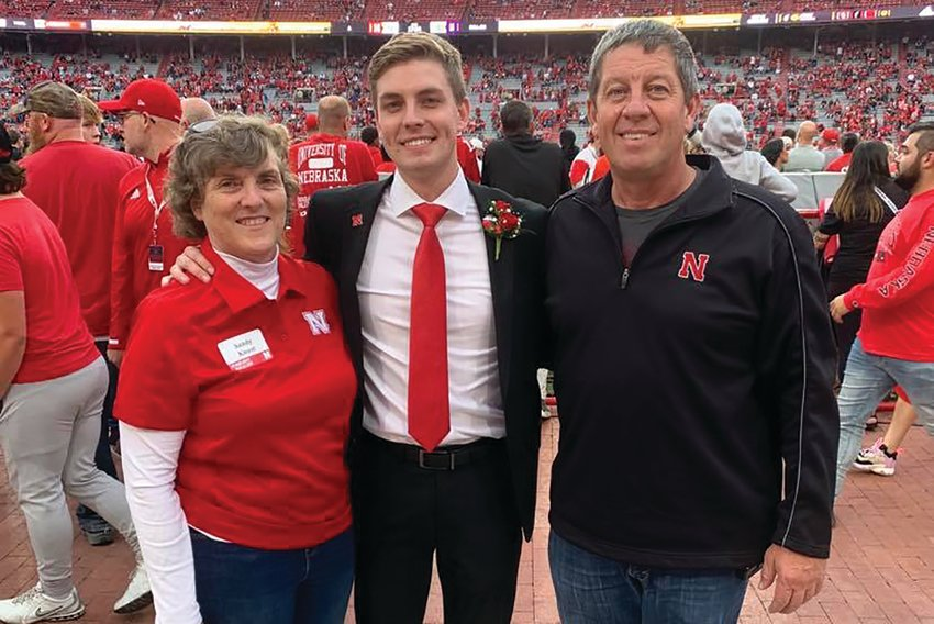 Riley Knust and his parents, Sandy and Rolan, stand for a photo in Memorial Stadium after the homecoming football game. Knust was a finalist for UNL's homecoming court.