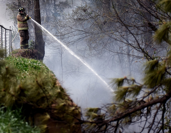 RANDY PARKER/THE DAILY TRIBUNE NEWS A Cartersville Fire Department firefighter douses flames of a fire that broke out Friday afternoon along the bank between the CSX railroad tracks and North Ave. in Cartersville.