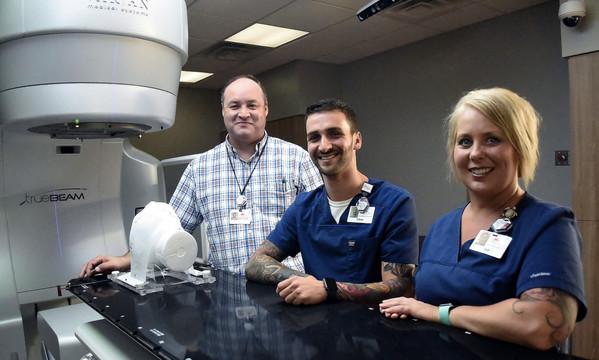 From left, Cartersville Medical Center dosimetrist Anthony Norcross, radiation therapist Chris Leone and lead radiation therapist Jodi Ward showcase the Hope Center's TrueBeam radiotherapy system.