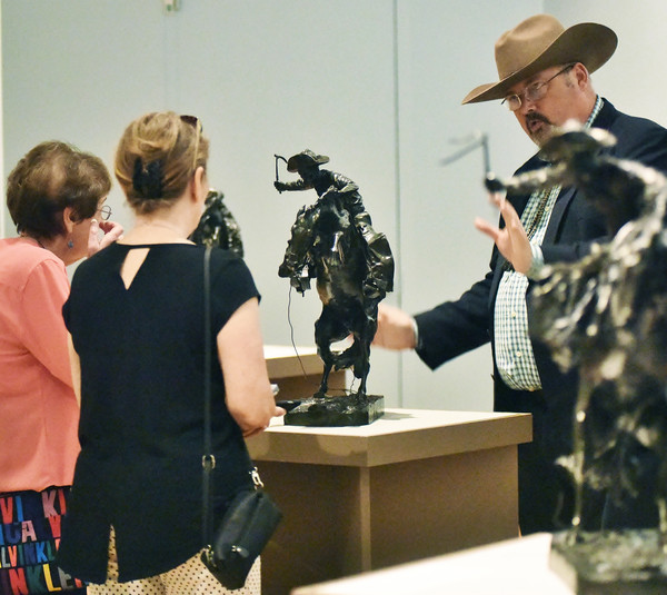 Booth Western Art Museum Executive Director Seth Hopkins explains some of the finer points and details of Frederic Remington's sculpture works to freelance writers Mickey Goodman, left, of Marietta, and Fran Kaplan of Atlanta.