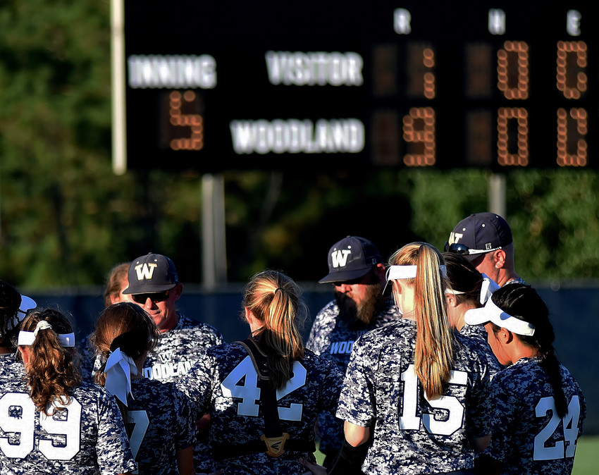 With the scoreboard at Wildcat Stadium reflecting another win behind them, the Woodland softball team listens to head coach Colman Roberts give a postgame speech on Monday evening.