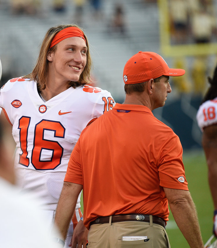 Clemson quarterback Trevor Lawrence speaks with Clemson head coach Dabo Swinney during a game against Georgia Tech Saturday in Atlanta. Clemson won 49-21 and Lawrence threw four touchdowns.