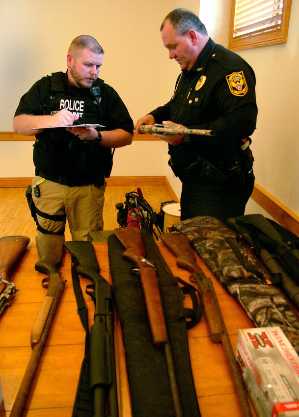 City of White Police Sgt. Chris Barnes, left, and Chief of Police Dane Hunter check serial numbers of some of the weapons stolen in a burglary ring.