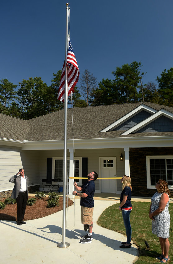 "U.S. Army Sgt. Robert ""Finn"" Visbal raises the American flag in front of his new residence that was custom built by Homes For Our Troops. Visbal's wife, Holley, second from right, and his mother, Sharon, look on as Homes For Our Troops Executive Director Bill Ivey, left, salutes."