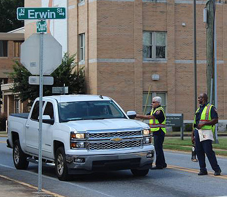 Sgt. Robbie Carlton, left, and firefighter Greg Reliford with the Cartersville Fire Department collect donations from motorists at the intersection of Erwin and Church streets during the Give Burns The Boot Campaign.