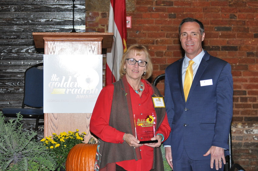 Bartow County Schools Director of Nutrition Services Pamela Blakeney and Superintendent Dr. Phillip Page show off the nutrition services department's first Platinum-level Golden Radish Award at a luncheon Monday at the Georgia Freight Depot in Atlanta. The department has won a Golden Radish for the fourth consecutive year.