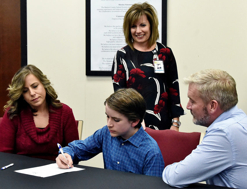 Woodland Middle School eighth grader Justus Young signs his REACH contract Thursday at the Bartow County College & Career Academy. Looking on at the table with him are his mother Amy Charleston and his father Luke Young. Also watching Justus sign is Kristy Mitchell, REACH Georgia Coordinator for Bartow County schools.