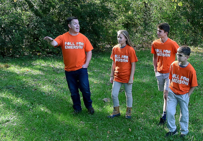 Frank Bennett, left, lead pastor of Lake Point Church, walks the property that will become Monroe Park in Emerson with his daughter, Marion, and sons Lawson, center, and Lincoln.