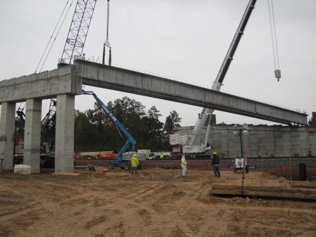 Workers place beams on the LakePoint Parkway extension bridge in Emerson Wednesday afternoon.