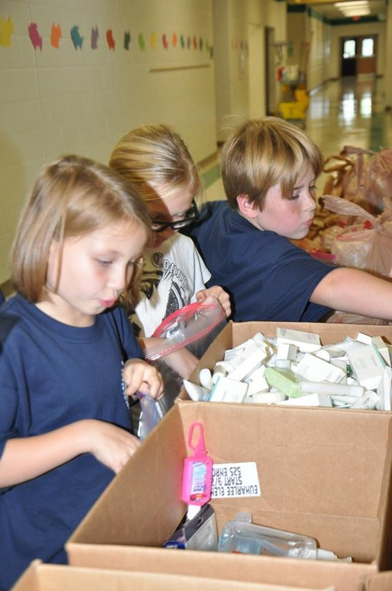 Euharlee student council members, from left, Brooklyn West, Faith Sumner and Nathan Cates gather up personal hygiene products for the Blessing Bags.