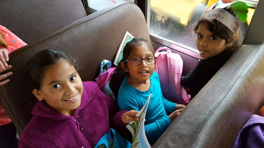 Hamilton Crossing student Jocelyn Mederos-Ortiz, left, reads a book to Ingrid Ramirez-Cruz, center, and Allisa Bonilla on one of their bus rides.