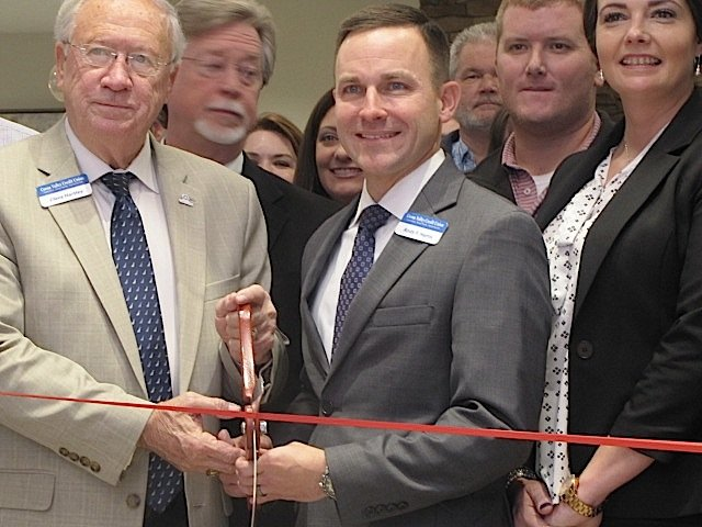 Coosa Valley Credit Union President and CEO Andy F. Harris, right, mans the scissors alongside CVCU Board of Directors Chairman Cleve Hartley at the Nov. 14 ribbon-cutting ceremony for the new West Cartersville location.