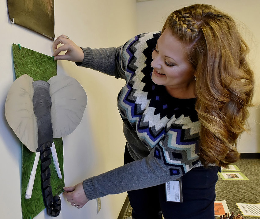 Woodland Middle School visual arts teacher Abby Hennington hangs her students' artwork at the Euharlee Welcome Center & History Museum.