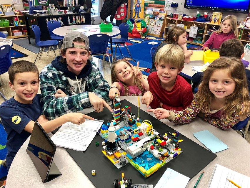 Cartersville High robotics team member Logan Warren, second from left, helps Cartersville Primary second-graders, from left, Will Galland, Kymburlyn Payne, Cash Meadows and Addison Bright work on the final portion of the energy section of the moon base they're building in their robotics program and plan their speaking parts for their presentation.