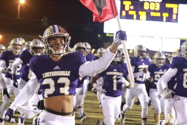 Cartersville senior Kaleb Chatmon carries a flag onto the field prior to a game earlier this season at Weinman Stadium. Chatmon and the Canes will face Blessed Trinity in the Class 4A state championship game at 4:30 p.m. Wednesday at Mercedes-Benz Stadium in Atlanta.