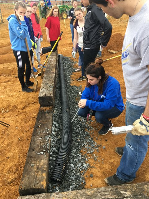 Students in Chuck Bohannon's AP environmental science class at Cass High School have spent class time as well as a number of Saturdays working on a butterfly garden that last year's class started as its final project. Here, they are preparing the drainage system underneath the garden.