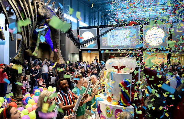 """RANDY PARKER/THE DAILY TRIBUNE NEWS More than 1,700 science lovers of all ages were on hand  as Tellus Science Museum celebrated it's tenth anniversary Saturday with a celebration that included the crowd singing """"Happy Birthday"""" and confetti being shot out of tubes. A large birthday cake was wheeled onto the floor of the museum's Great Hall, from which Terry the Pteranodon emerged to welcome all in attendance."""