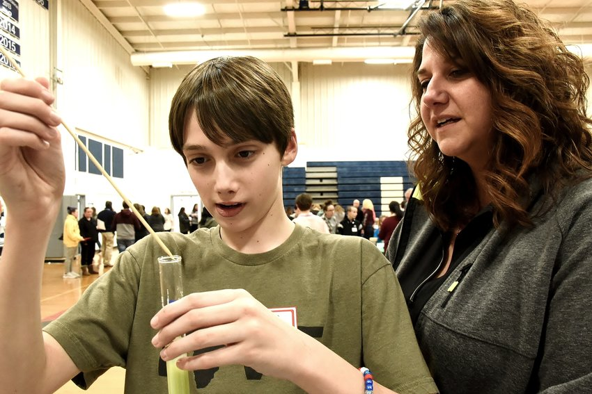 As his mother Kristy watches, Woodland Middle School seventh-grader Caleb Underwood extracts DNS from a kiwi fruit at the school's STEAM night Thursday.