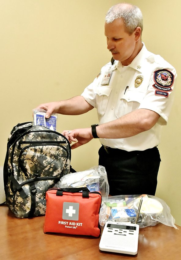 Cartersville Fire Marshal Mark Hathaway examines items in his emergency preparedness backpack.