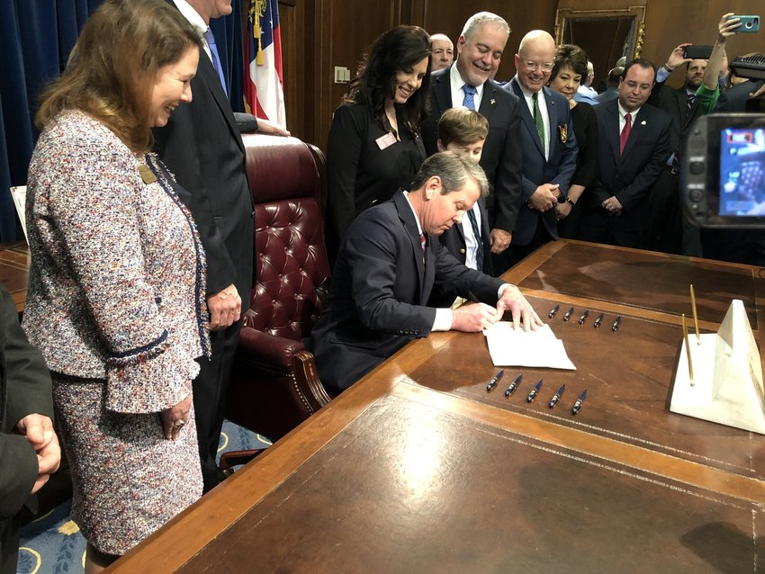 Surrounded by supporters, Gov. Brian Kemp signs into law Senate Bill 25, which reverses last year's House Bill 978 and once again makes it illegal to pass a stopped school bus on a roadway divided by a turn lane.