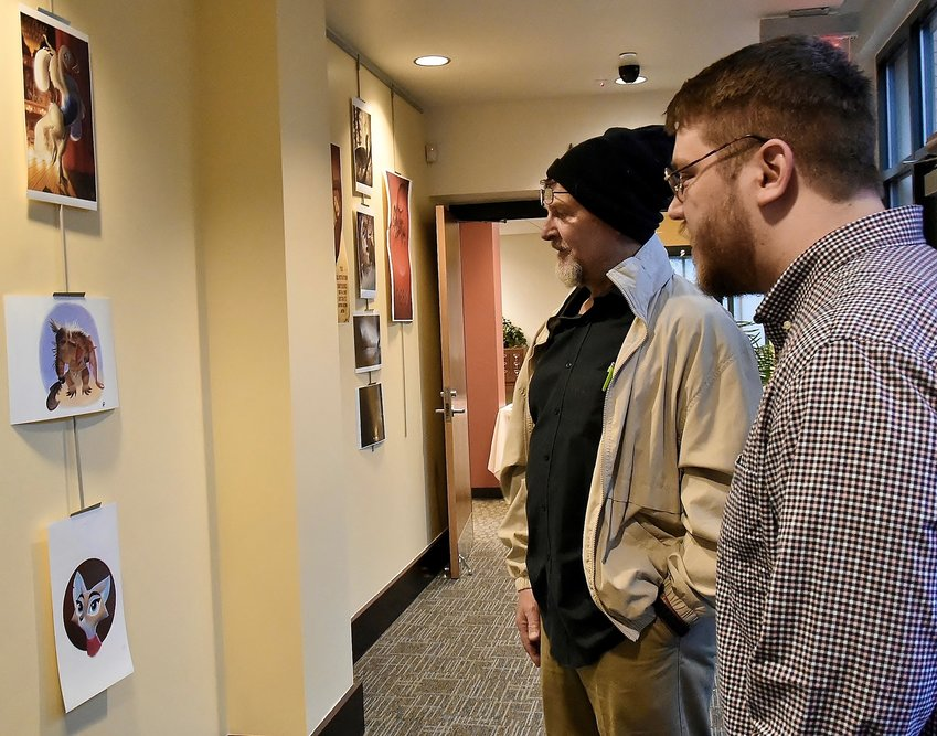 Illustrator and sculptor Keller Pyle, right, talks with Barry Webb of Cartersville about some of the pieces in his exhibit at the Cartersville Public Library through March 31.