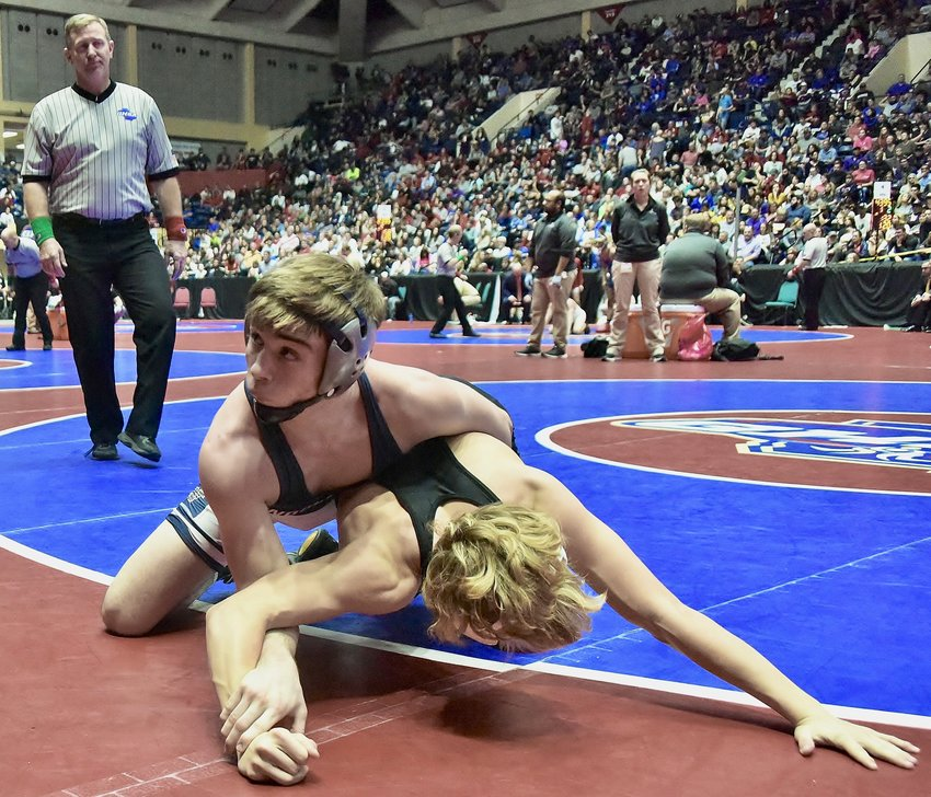 Woodland senior Kyle Gollhofer wrestles in the Class 5A 120-pound weight division championship match Saturday in Macon. Gollhofer eased to a major-decision win to capture his fourth individual state title, making him the first wrestler to accomplish that feat in Woodland history.