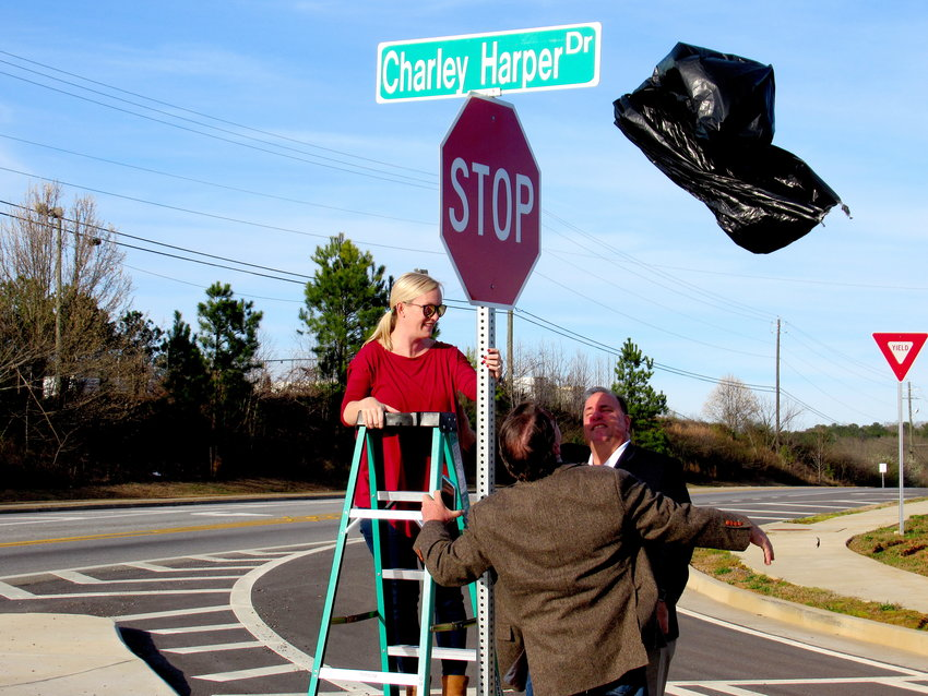 Leah Harper Bush — with some assistance from Cartersville Mayor Matt Santini and her late father's business partner Mark Harris — unveils the new street sign for Charley Harper Drive in West Cartersville on Monday afternoon.