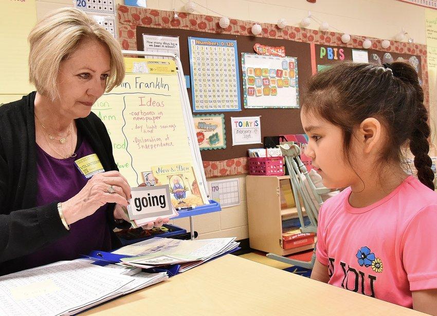 Read to Grow volunteer Carol Branton uses flash cards to help Cloverleaf Elementary first-grader Iliana Gamez develop sharper reading skills.